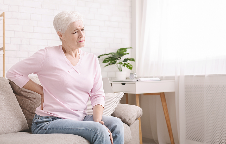 Woman sitting on couch with back pain