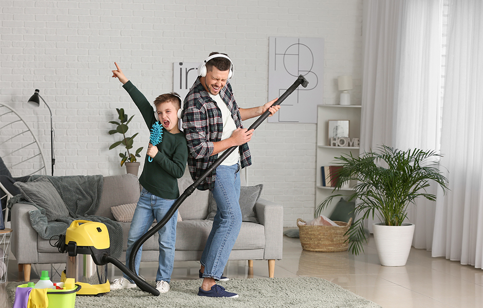 Father and son singing as they clean living room